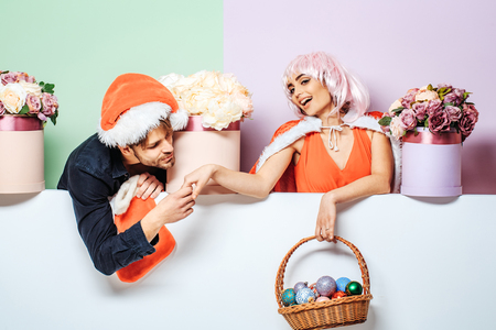 plaything: young christmas couple of santa claus bearded man in red hat and pretty sexy girl in pink wig with cute smiling face near new year decoration balls in basket flowers in box and xmas stocking or sock