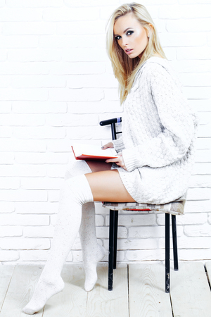 sexy sweater: Pretty girl or beautiful cute woman fashion model with blond hair in sexy knitted sweater reads red book sitting on chair on white brick wall