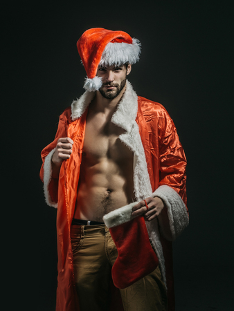 Handsome santa claus guy sexy young bearded macho christmas man model in red xmas or new year coat and hat has bare muscular torso and chest on black background holds stocking or sock