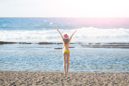 sexy santa claus: sexy santa claus cute girl or pretty young woman in red new year hat and yellow swimsuit celebrates christmas or xmas holidays at sand beach near sea or ocean water sunny outdoor on natural background Stock Photo