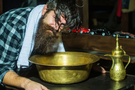 Handsome man, hipster, with beard washes hair in vintage, copper basin in barber shop