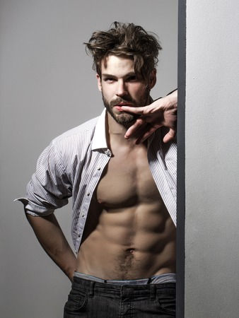 unbutton: Thoughtful handsome man with beard or blond muscular macho athlete bodybuilder in unbutton shirt points to six packs and abs on muscle torso on white background