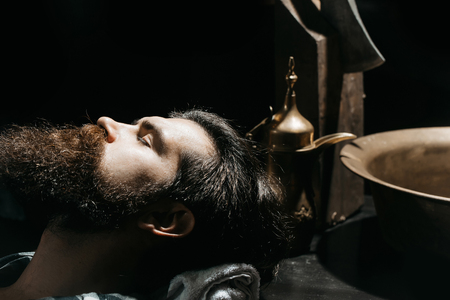 Handsome bearded man, hipster, brunette with beard and moustache ready for shave in barbershop. Barber or shaver tools copper basin, water jug, axe on table