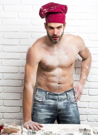 Knappe man of gespierd kok, bakker, in de rode chef hoed poseert met bloem op sexy, spier torso, lichaam, met zes packs en abs op keuken muur Stockfoto
