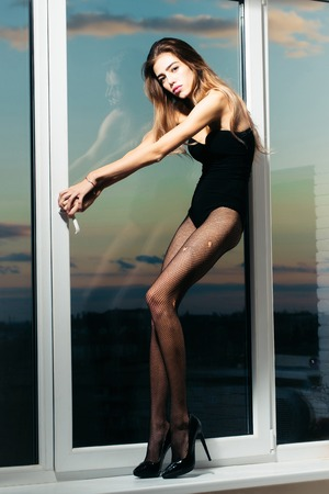 Pretty sexy girl young cute slim woman with long beautiful hair and legs in black fishnet tights fashionable shoes and lingerie poses at window on blue sky background Stock Photo