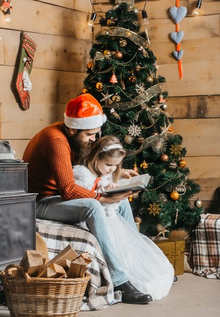 christmas father and daughter in red santa claus hat and sweater reading book at xmas decorated tree. bearded man with cute girl child at new year holidays celebration near basket with wood
