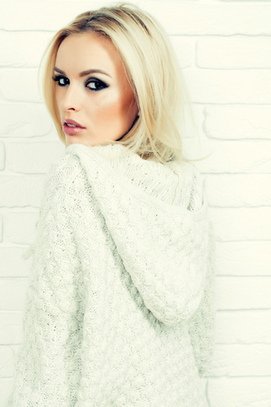 sexy sweater: Pretty girl or beautiful cute woman fashion model with blond hair in sexy knitted sweater poses on white brick wall background
