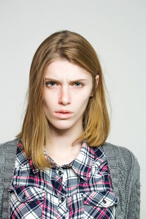 frowns: Upset pretty girl or cute beautiful woman female model with blonde hair in plaid shirt and knitted coat frowns on grey background