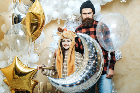 smiling christmas cute small girl or pretty child in winter hat and serious bearded man in checkered shirt, near silver, gold and white balloons and decorative new year snowflakes, holds wooden sledge