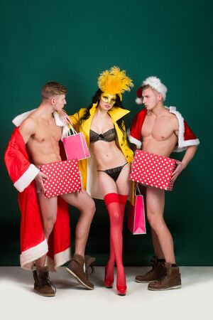 Pretty girl or beautiful woman in golden, carnival mask with feathers and sexy lingerie. Handsome, muscular men with muscle bodies in santa suits with Christmas presents on green wall