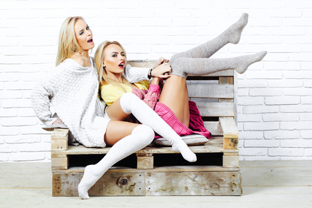 Pretty winking girls or two sexy cute women with blond hair in home sweaters and socks sit on wooden pallet sofa on white brick wall Stock Photo