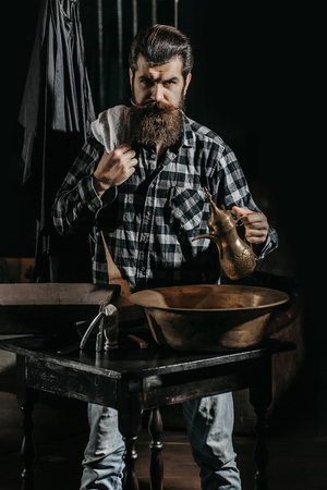 Handsome man, bearded hipster, brunette with long beard and moustache holds copper jug and towel on dark background