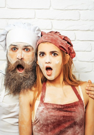 Surprised, handsome man, cook or baker with flour on face, beard and moustache and messy, pretty girl or beautiful woman with open mouths on white kitchen wall