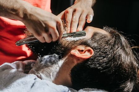 Handsome bearded man, hipster, brunette with beard and moustache has shave in barbershop. Barber works with vintage razor and shaving foam Stock Photo