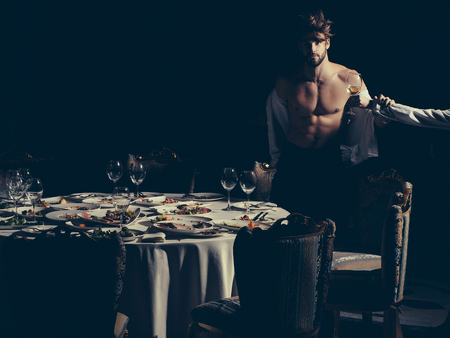 unbutton: Female hand with wine glass and handsome man or sexy muscular macho athlete in unbutton shirt at table with leftovers food on dirty plates after banquet in restaurant on dark background