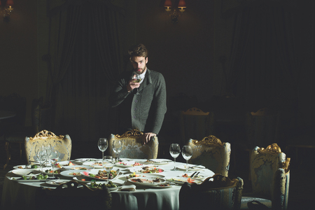 dirty blond: Handsome young man with beard and blond hair drinks wine from glass over table with leftovers or residues food on dirty plates after banquet dinner in restaurant on dark background