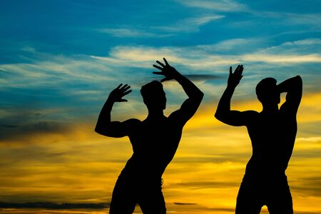 muscular men or bodybuilders silhouettes, handsome, young, male athlete people with sexy torso outdoors in sunset sky Stock Photo