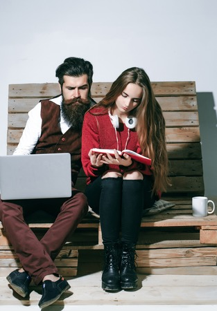 conferencing: Young couple spend time together on wooden pallet sofa. Handsome man, bearded hipster with beard uses laptop, computer. Pretty girl or beautiful woman reads book