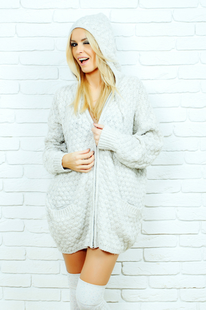 sexy sweater: Pretty smiling girl or beautiful cute woman fashion model with blond hair in sexy knitted sweater poses on white brick wall background Stock Photo