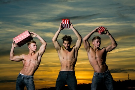 three men or bodybuilders, handsome, young, male athlete people with sexy, muscular torso outdoors in sunset sky. guys holds red present boxes for valentines or christmas holidays