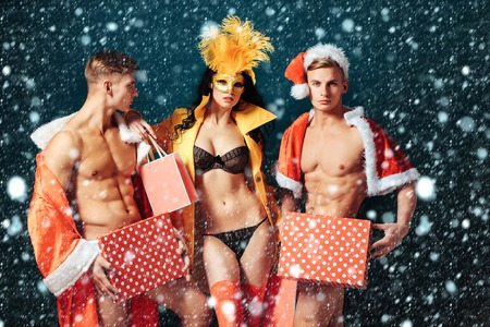 Pretty girl or beautiful woman in golden, carnival mask with feathers and sexy lingerie. Handsome, muscular men with muscle bodies in santa suits with Christmas presents on blue wall under snow Stock Photo