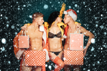 Pretty girl or beautiful woman in golden, carnival mask with feathers and sexy lingerie. Handsome, muscular men with muscle bodies in red santa suits with Christmas presents on blue wall under snow