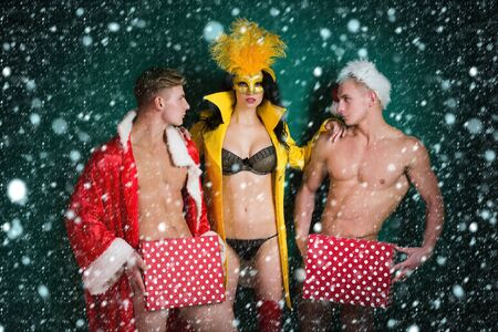 Pretty girl or beautiful woman in golden, carnival mask with feathers and sexy lingerie. Handsome, muscular men with muscle bodies in santa suits with Christmas presents on green wall under snow