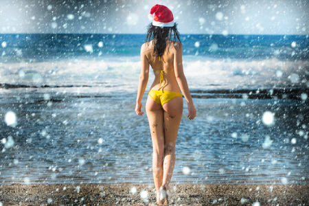 sexy santa claus cute girl or pretty young woman in red new year hat and yellow swimsuit celebrates christmas or xmas holidays at sand beach near sea or ocean water on natural background under snow