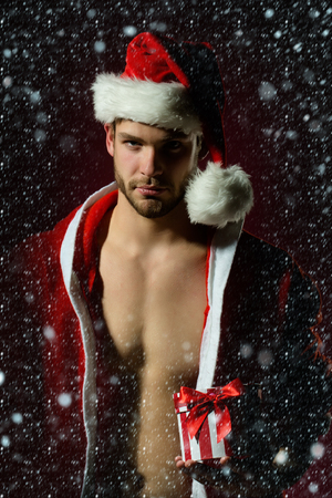nackte brust: Weihnachten schön sexy neuen Jahr jungen muskulösen Mann mit nacktem Oberkörper in der roten Weihnachtsweihnachtsmann-Wintermantel und Hut hält unter Schnee und Schneeflocken present box