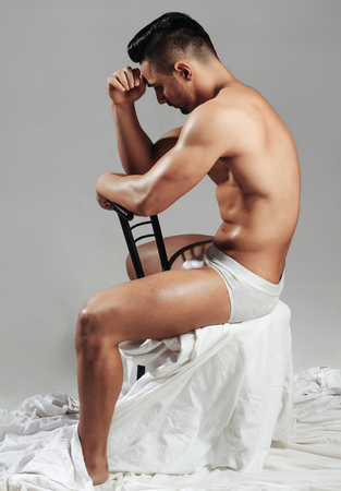 oily: Handsome man or muscular bodybuilder, macho, with sexy, muscle torso, body, with six packs and abs, triceps, biceps, with oily skin in white sexi underpants sits on chair on grey background