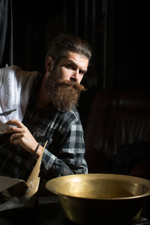 Handsome bearded man, hipster, brunette with long beard and moustache with towel and copper basin on dark background