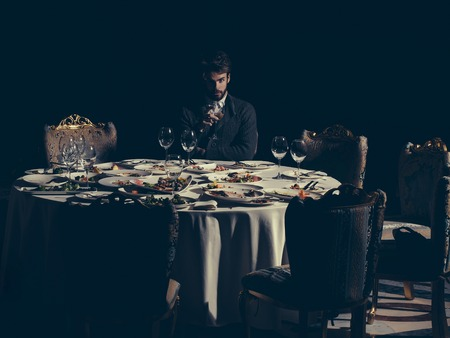 dirty blond: Handsome young man with beard and blond hair drinks wine from glass sitting at table with leftovers or residues food on dirty plates after banquet dinner in restaurant on dark background Stock Photo