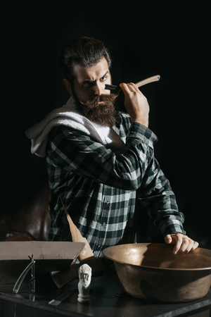 Handsome man, bearded hipster, brunette with long beard and moustache shaves with open vintage razor with blade on dark background Stock Photo