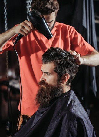 Handsome barber drying hair with drier, makes hairstyle, to bearded man with beard. Male customer sitting in chair in hairdressing saloon or barbershop Stock Photo