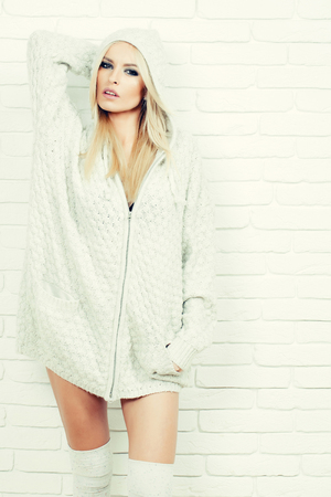 Pretty girl or beautiful cute woman fashion model with blond hair in sexy knitted sweater poses on white brick wall background