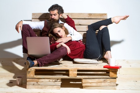 Young couple spend time together on wooden pallet sofa. Handsome man, bearded hipster with beard, and pretty girl or beautiful woman use laptop, computer