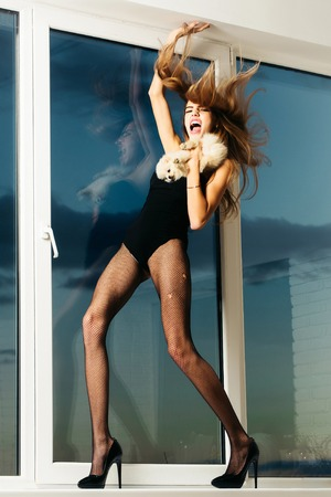 Pretty sexy girl cute slim shouting woman has pink lips with long hair and legs in black fishnet tights fashionable shoes and lingerie at window on blue sky background holds small dog or puppy pet Stock Photo