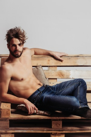 macho: Young handsome man or muscular macho with sexy torso, sits on wooden, pallet sofa on grey background in jeans