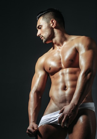 Handsome man or muscular macho, bodybuilder, with sexy, muscle torso, body, with six packs and abs poses on grey background in white panties Stock Photo