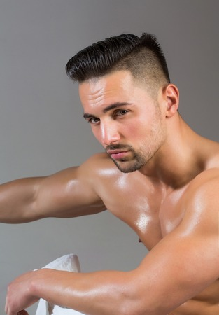 macho: Handsome man or muscular macho, bodybuilder, with sexy, wet, muscle torso, body, chest and hands poses on grey background Stock Photo