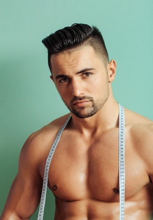 muscle belly: Handsome man or muscular macho, bodybuilder, with sexy, muscle torso, body, with six packs and abs poses on green background with tape measure on belly. Dieting and healthy lifestyle