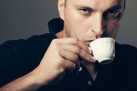 unshaven: handsome sexy man or guy with stylish hair on serious unshaven face in shirt drinking coffee from white cup on grey background, closeup