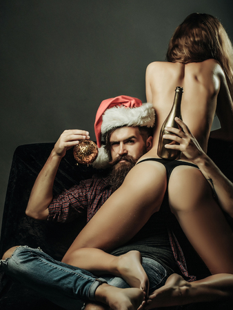 handsome bearded man with long beard in red christmas santa claus hat near young woman with sexy body and buttocks with golden wine or champagne bottle on bare back in lingerie on grey background