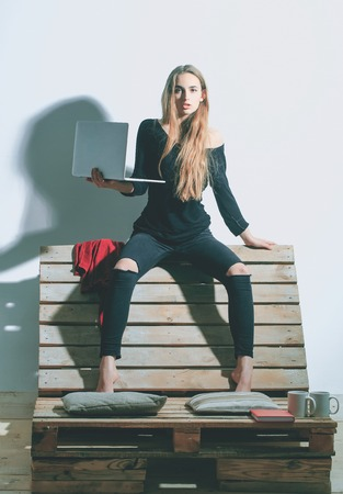 conferencing: Pretty girl or beautiful woman, cute, sexy, fashion model with long hair in casual clothes with laptop, computer, sits on backrest of wooden, pallet sofa on white wall Stock Photo