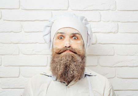 ハンサムな狂気の男、コックやシェフの制服で顔、ひげと口ひげのポーズに小麦粉と白いレンガの壁に帽子とパン屋 写真素材
