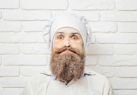 Handsome crazy man, cook or baker with flour on face, beard and moustache poses in chef uniform and hat on white brick wall