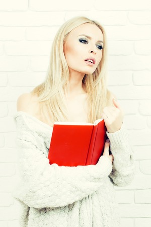 sexy sweater: Pretty girl or beautiful cute woman fashion model with blond hair in sexy knitted sweater reads red book on white brick wall