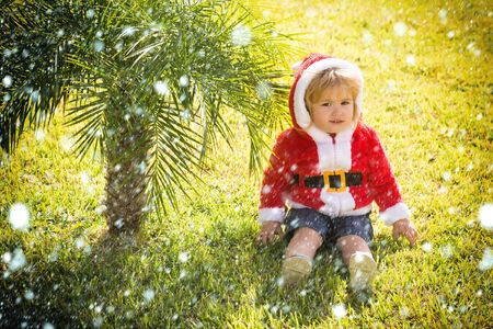 small santa claus cute boy or child in red new year coat with white fur and hood celebrates christmas or xmas holidays near green palm tree on grass sunny outdoor on natural background under snow Stock Photo