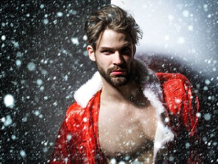 unbutton: Handsome man with beard or blond muscular macho athlete bodybuilder in unbutton santa suit with six packs and abs on muscle torso on white background under snow and snowflakes