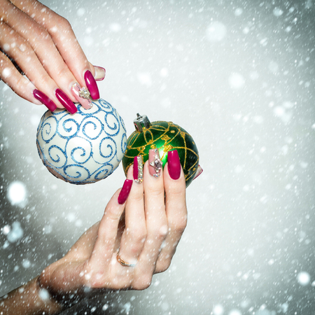christmas manicure: Female hands with fingernail manicure hold beautiful blue and green Christmas baubles with ornament traditional xmas new year decoration balls under snow and snowflakes isolated on white